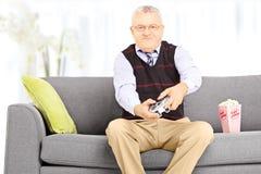 Homme supérieur assis sur un sofa jouant des jeux vidéo à la maison Photographie stock