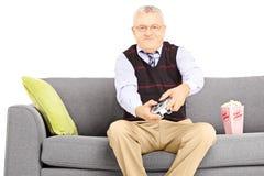 Homme supérieur assis sur un sofa jouant des jeux vidéo Photo stock