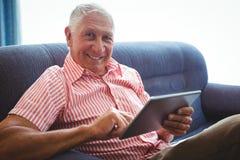 Homme supérieur assis sur un sofa regardant l'appareil-photo Photographie stock