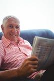 Homme supérieur assis sur un sofa regardant l'appareil-photo tout en tenant le journal Images stock