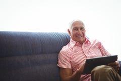 Homme supérieur assis sur un sofa tout en tenant le comprimé numérique Image stock