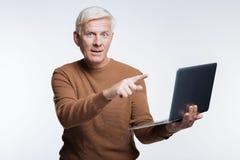 Homme supérieur aux cheveux blancs se dirigeant à l'ordinateur portable Photographie stock libre de droits