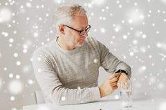 Homme supérieur avec de l'eau et pilule regardant la montre Photo stock