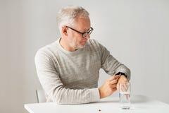 Homme supérieur avec de l'eau et pilule regardant la montre Photos stock