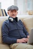 Homme supérieur avec des écouteurs Photographie stock libre de droits