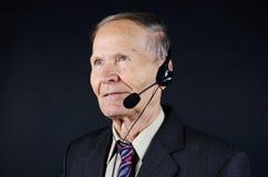 Homme supérieur avec des écouteurs sur le fond noir Image stock