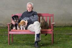 Homme supérieur avec des animaux familiers Photos stock
