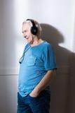 Homme supérieur avec des mains dans des poches utilisant des écouteurs Photographie stock libre de droits