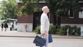 Homme supérieur avec des paniers marchant dans la ville clips vidéos