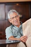 Homme supérieur avec des verres lisant le journal Images libres de droits
