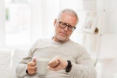 Homme supérieur avec du café regardant la montre-bracelet Images stock