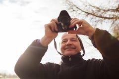 Homme supérieur avec l'appareil-photo dans la ville Il fait la photo Photos libres de droits