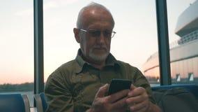 Homme supérieur avec l'embarquement de attente de cheveux gris et de barbe grise dans l'aéroport, passant le temps à l'aide du sm banque de vidéos