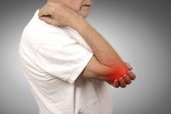 Homme supérieur avec l'inflammation de coude coloré dans la douleur rouge de la douleur Photo stock