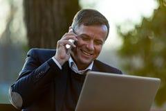 Homme supérieur avec l'ordinateur portable et le mobile dehors Photographie stock