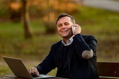 Homme supérieur avec l'ordinateur portable et le mobile dehors Photographie stock libre de droits