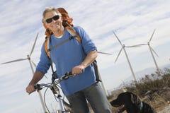 Homme supérieur avec la bicyclette à la ferme de vent Images stock