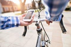 Homme supérieur avec la bicyclette d'équitation de smartphone en ville Photo libre de droits