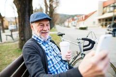 Homme supérieur avec la bicyclette en ville, prenant le selfie avec le téléphone intelligent Images libres de droits