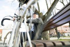 Homme supérieur avec la bicyclette en ville, se reposant sur le banc avec du café Photos stock