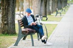 Homme supérieur avec la bicyclette en ville, tenant le téléphone intelligent, textotant Photo libre de droits