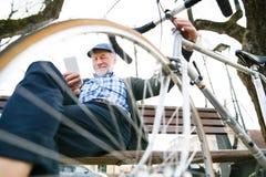 Homme supérieur avec la bicyclette en ville, tenant le téléphone intelligent, textotant Image stock