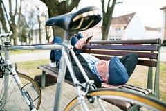 Homme supérieur avec la bicyclette en ville, tenant le téléphone intelligent, textotant Images libres de droits