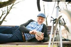 Homme supérieur avec la bicyclette en ville, tenant le téléphone intelligent, textotant Photographie stock