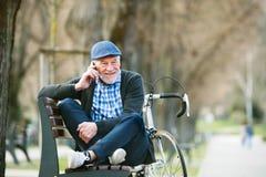 Homme supérieur avec la bicyclette et le téléphone intelligent, faisant l'appel téléphonique Photographie stock libre de droits