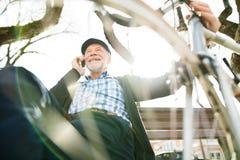 Homme supérieur avec la bicyclette et le téléphone intelligent, faisant l'appel téléphonique Image libre de droits