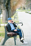 Homme supérieur avec la bicyclette et le téléphone intelligent, faisant l'appel téléphonique Photographie stock