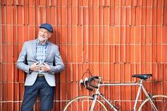 Homme supérieur avec la bicyclette se tenant contre le mur de briques Images stock