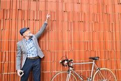 Homme supérieur avec la bicyclette se tenant contre le mur de briques Images libres de droits