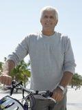 Homme supérieur avec la bicyclette sur la plage tropicale Photos libres de droits