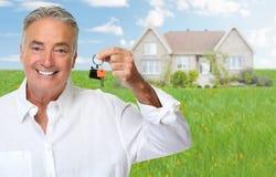 Homme supérieur avec la clé de maison photographie stock