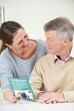 Homme supérieur avec la fille adulte regardant la brochure pour Retiremen photos libres de droits