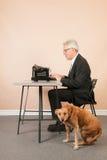 Homme supérieur avec la machine à écrire antique Photographie stock