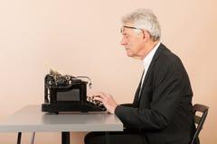 Homme supérieur avec la machine à écrire antique Images stock