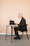 Homme supérieur avec la machine à écrire antique Images libres de droits