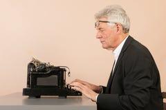 Homme supérieur avec la machine à écrire antique Photo stock