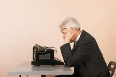 Homme supérieur avec la machine à écrire antique Photos stock