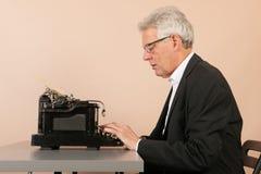 Homme supérieur avec la machine à écrire antique Image libre de droits