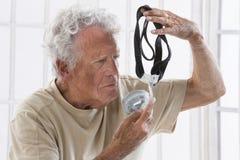 Homme supérieur avec la machine d'apnea de sommeil Images stock