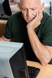 Homme supérieur avec la main sur Chin Using Computer In Classroom Photographie stock libre de droits