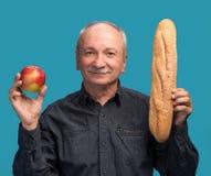 Homme supérieur avec la pomme et la baguette Images stock