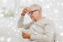 Homme supérieur avec la tasse de thé à la maison Photographie stock libre de droits