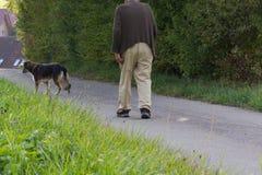 homme supérieur avec le bâton de marche et le chien de berger allemand à coté Images stock