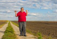 Homme supérieur avec le bâton de marche se tenant sur une route de campagne photographie stock