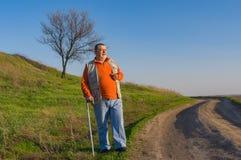 Homme supérieur avec le bâton de marche se tenant sur une route de terre Photos stock