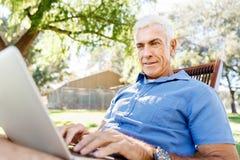 Homme supérieur avec le carnet se reposant en parc Photo libre de droits